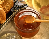 A Wooden Spoon Scooping Honey From a Glass Bowl