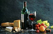 Red wine still life with cheese, fruit and baguette