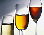 Three glasses of different heights with white, rose & red wine