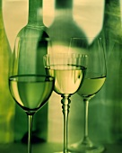 Three white wine glasses in front of bottle silhouette