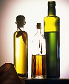 Three bottles of olive oil against a grey backdrop