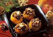 Four baked apples stuffed with raisins and nuts in a baking dish
