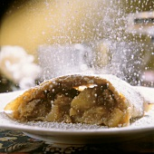 A piece of apple strudel being sprinkled with icing sugar