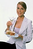 Young woman holding Martini glass & sandwiches
