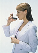 Blond woman in white suit drinking red wine; profile