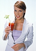 Frau in weißem Kostüm trinkt Gemüsecocktail durch Strohhalm