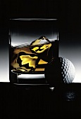 Glass of Whiskey on the Rocks; Golf Ball