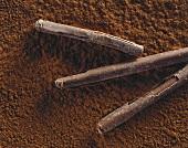 Three chocolate rolls on cocoa powder
