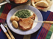 Pork Chop with Potatoes in their Skins & Peas on Plate
