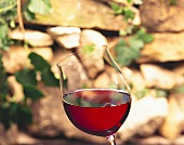 Red wine glass held at an angle in front of stone wall
