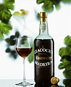 A bottle of Madeira and a half-filled glass