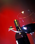 Red wine glass in front of a red wine bottle and fork with olive