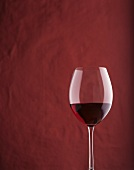 A filled red wine glass against red background