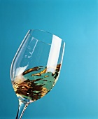 Swirling a glass of white wine against a blue background