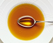 Sweet and sour duck consommé in plate with spoon