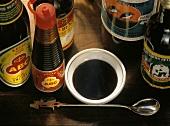 A Bowl of Kecap with Assorted Bottles of Kecap