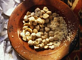 Whole and Ground Kemiri Nuts in a Bowl