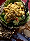 Currynudeln mit Hühnerfleisch auf Teller & Bananenblättern