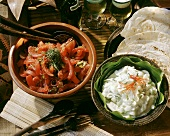 Tomato and Mint Salad and Cucumber in Yogurt Dressing in bowls with Flour Tortillas