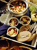 Fancy Bouillabaisse: French Fish Soup in Tureen and in Bowls with white Bread Slices coated with Garlic Mayonnaise on Tray