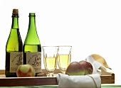 Two bottles and two glasses of French cider on tray