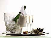 Champagne in an Ice Bucket with Two Glasses and Olives
