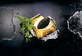 Baked potato with crème fraiche and black caviare in foil