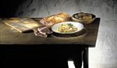 Ein Teller Nudeln mit Champignons & Schinken auf Holztisch