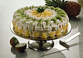 Kiwi fruit and pineapple cream gateau on cake stand