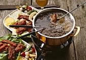 Spareribsfondue: Fonduegabel mit Fleisch im heißem Öl
