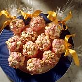 Süße Popcornkugeln, einige in Cellophan verpackt, auf Teller