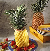 A whole fresh pineapple cut in a swirl pattern with berries