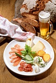 Mixed Appetizer Plate with Ham, Salami, Cheese, and Vegetables with dark Bread and Glass of Beer