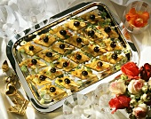 Polenta rhombuses with black Olives as party bite-size Snacks Tray