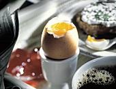 Ein gekochtes Ei im Eierbecher auf dem Frühstückstisch