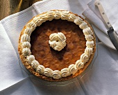 A pumpkin pie decorated with cream edge