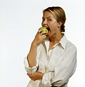 Woman Biting into a Granny Smith Apple