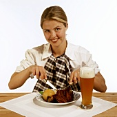 Model with pork knuckle & dumpling on plate, glass of Weissbier