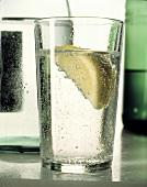 Ein Glas Mineralwasser mit Zitronenschnitz