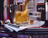 Glen Grant whisky with ice in bar, whisky bottles on bar