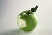 A Granny Smith Apple That Has Been Bitten; Water Drops