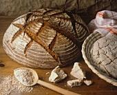 Ein dunkles Brot, Hefe & Teig auf Holztisch