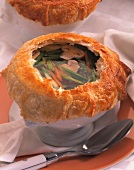 Vegetable and mushroom soup under puff pastry topping