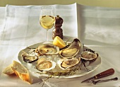 Oysters and lemon on ice on plate, wine glass on table
