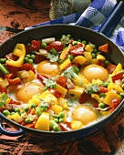 Pan-cooked vegetables with fried eggs in the pan