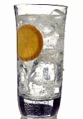 Mineral water with ice cubes and orange slice in glass