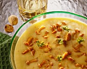 Cream of chanterelle soup with parsley in glass dish