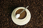 Cup of coffee with milk & spoon with sugar on coffee beans