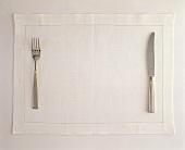 Messer und Gabel an ihrem Platz auf einem weissen Tischset