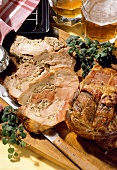 Roast pork roll with onion & mushroom stuffing on wooden board